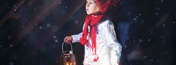 Sweet boy, holding a lantern, looking at a light coming through
